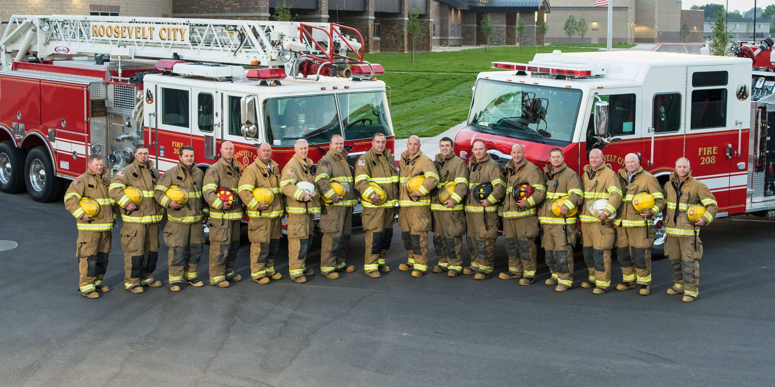Members of the Roosevelt Fire Department pictured with two fire trucks in the summer of 2019