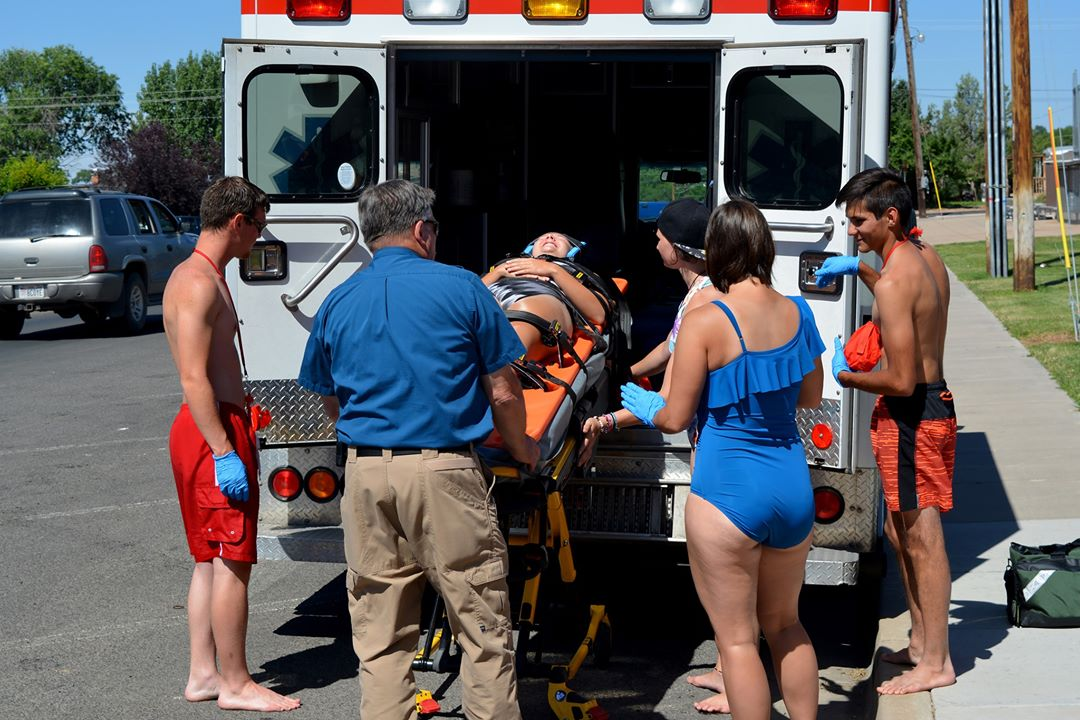 Lifeguards and emergency response personnel load a girl on a backboard into an ambulance.